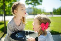 Two sisters having fun with drinking water fountain on warm and sunny summer day stock image