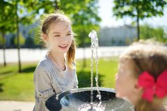 Two sisters having fun with drinking water fountain on warm and sunny summer day stock photography