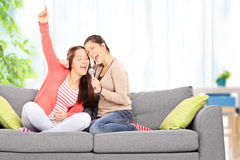 Two sisters having fun singing on microphone Stock Photo