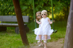 Two sisters having fun on a swing on summer day Stock Image