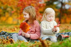 Two sisters having fun together in autumn park Stock Photos