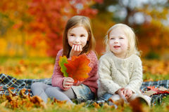 Two sisters having fun together in autumn park Royalty Free Stock Photography