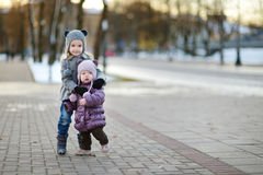 Two sisters having fun at winter city Stock Images
