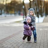 Two sisters having fun at winter city Royalty Free Stock Photography