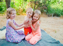 Two sisters hold a brother Royalty Free Stock Photography