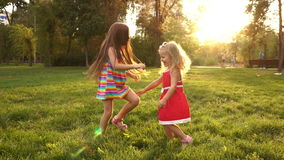 Two sisters holding hands circling. On the lawn in the city park outdoors. Freedom and carefree. Happy childhood stock footage