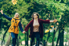 Two sisters holding hands while walking in the autumn park. Girls are holding a bouquet of maple leaves, they stroll in the park Royalty Free Stock Image