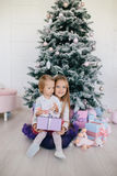 Two sisters at home with Christmas tree and presents. Happy children girls with Christmas gift boxes and decorations. Royalty Free Stock Photo