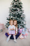 Two sisters at home with Christmas tree and presents. Happy children girls with Christmas gift boxes and decorations. Royalty Free Stock Photos