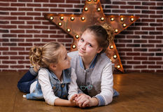 Two sisters at home in front brick wall. Two girls sisters are posing in front brick wall and lightning decorative star Royalty Free Stock Images