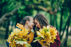 Two sisters hug, with a bunch of leaves in the park. Young girls standing in a park with a bunch of leaves, two sisters embrace. Love, family Stock Photography