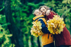 Two sisters hug, with a bunch of leaves in the park. Young girls standing in a park with a bunch of leaves, two sisters embrace. Love, family stock photos