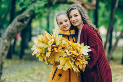 Two sisters hug, with a bunch of leaves in the park. Young girls standing in a park with a bunch of leaves, two sisters embrace. Love, family Stock Images