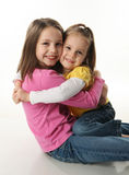 Two sisters hugging. Two cute young sisters hugging each other, isolated on white Stock Image