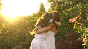 Two sisters hugging in the garden. Two sisters in white dresses hug each other in the garden after a long separation. Happiness of a family meeting stock footage