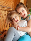 Two  sisters hugging. Two little sisters sitting embracing each other at home Royalty Free Stock Images