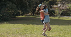Two sisters hugging outdoors on the grass. Slow motion shot of Two sisters hugging outdoors on the grass stock video footage