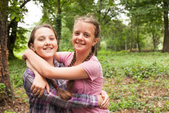 Two sisters hugs. Two teenager sisters smiling and hugging each other in summer city park Stock Photos