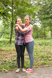 Two sisters hugs. Two teenager sisters smiling and hugging each other in summer city park Royalty Free Stock Photography