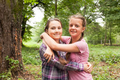 Two sisters hugs. Two teenager sisters smiling and hugging each other in summer city park Stock Photography