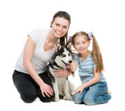 Two sisters and a husky dog Stock Photos