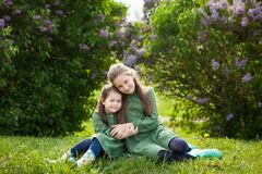 Free Two Sisters In Green Linen Dress Have Fun In The Park With Blooming Lilacs, Enjoy Spring And Warmth Stock Image - 173309601