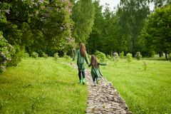 Free Two Sisters In Green Linen Dress Have Fun In The Park With Blooming Lilacs, Enjoy Spring And Warmth Stock Photos - 173309873