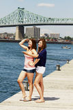 Two sisters interacting with bridge behind Stock Photography