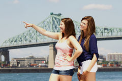 Two sisters interacting with bridge behind Royalty Free Stock Photos