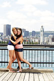 Two sisters interacting with city behind Royalty Free Stock Image