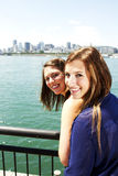 Two sisters interacting with city behind Royalty Free Stock Photos
