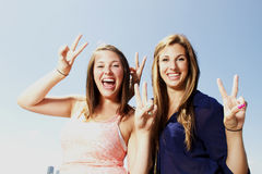 Two sisters interacting making peace sign Royalty Free Stock Photography
