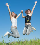 Two sisters in jeans jumping outdoors Royalty Free Stock Images