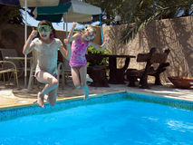 Two Sisters Jumping in the Pool Stock Photos