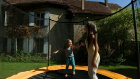 Two sisters jumping on the trampoline stock video footage