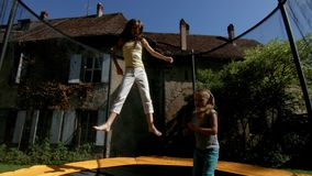 Two sisters jumping on the trampoline stock video