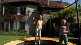 Two sisters jumping on the trampoline stock footage