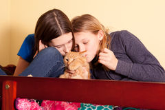 Two sisters kissing cat Royalty Free Stock Image