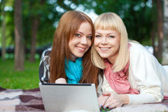 Two sisters with laptop in the park Stock Photos