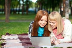 Two sisters with laptop in the park Stock Photography
