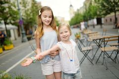 Two sisters laughing and hugging on warm and sunny summer day in a city. Cute siblings having a good time together royalty free stock photos