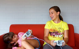 Two Sisters laughing, playing video games. Two girls playing video game. One teen one child. White wall and red sofa. Laughing together Stock Photo