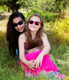 Two sisters laying down in the park Royalty Free Stock Photo