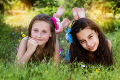 Two sisters laying down in the park Royalty Free Stock Photography