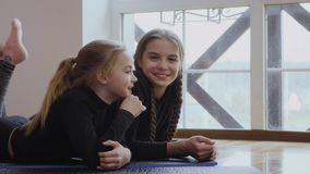 Two little sisters lays on floor and talking. Two sisters lays on floor. The girls are talking with each other. Cute children lays near panoramic window and stock video