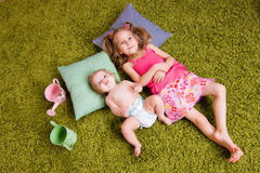 Two sisters lie on carpet Stock Photography