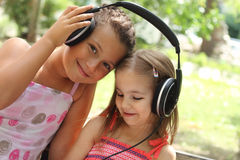 Two sisters listen to the music outdoor Royalty Free Stock Photography
