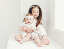 Two sisters little girls in white room at home Royalty Free Stock Image