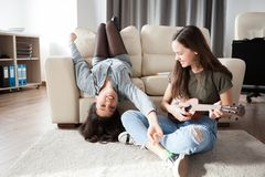 Two sisters in the living room having fun Royalty Free Stock Photography