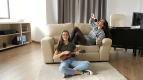 Two sisters in the living room having a good time. One is playing at ukulele while the other is singing at a microphone on the sofa. Slow motion footage stock footage